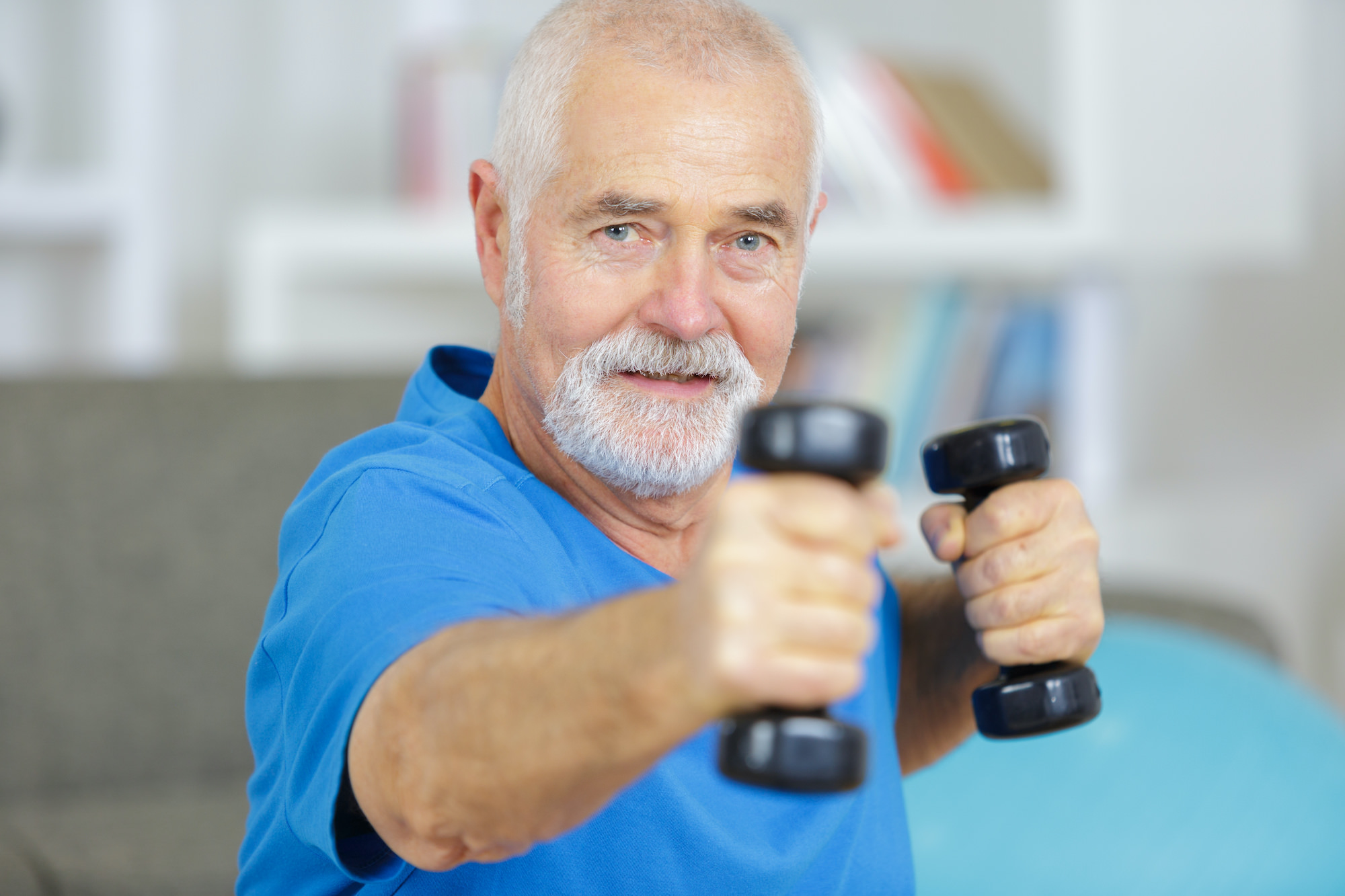 elderly man exercising with dummbells at home
